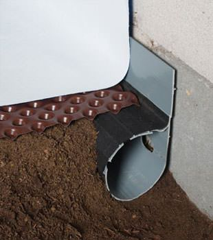 Closeup of a crawl space drainage system installed in Mooneyham